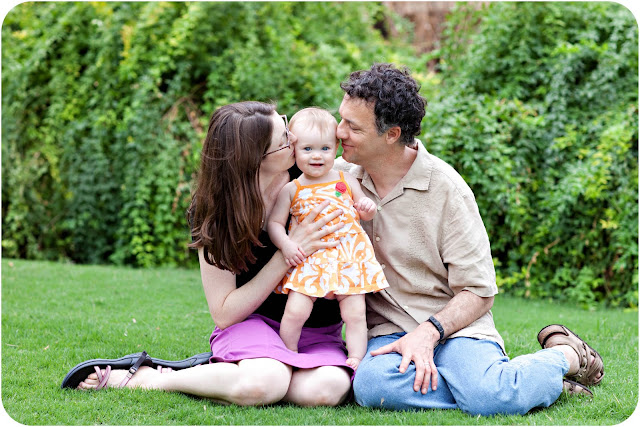 Candid shot of tender moment between child and parents during family photo session
