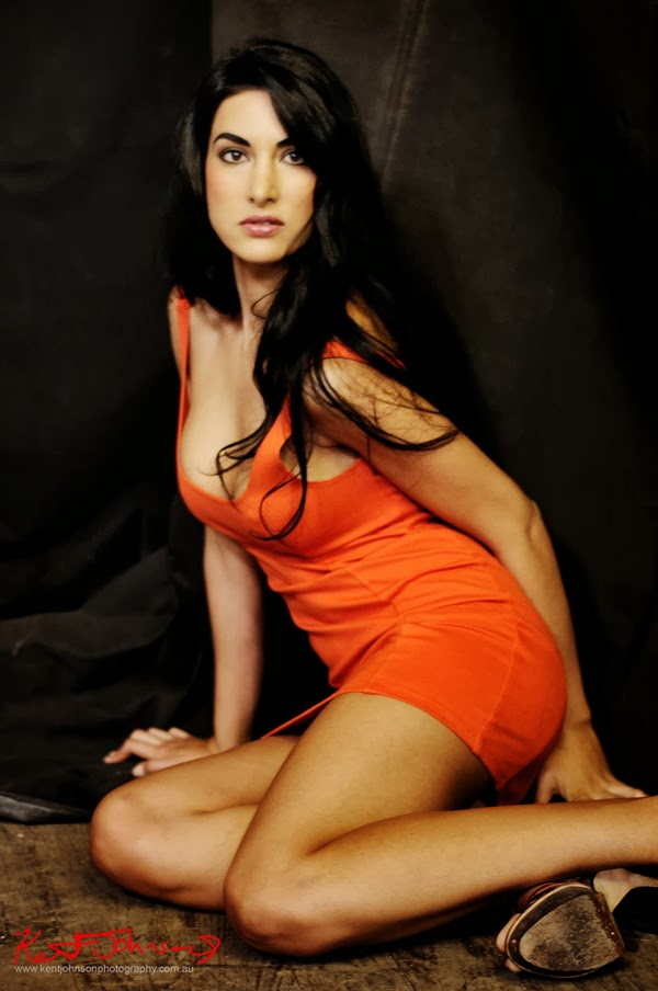 Sensual look, seated on floor in orange body con dress against a black background. Photographed by Kent Johnson.