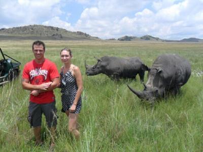 BEYER (kanan) dan suaminya bergambar di depan dua ekor badak sumbu di Taman Semula Jadi Aloe Ridge dekat Johannesburg baru-baru ini.