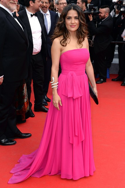 Salma Hayek in a pink Saint Laurent gown with Boucheron jewels and a Saint Laurent black studded clutch at Cannes 2014