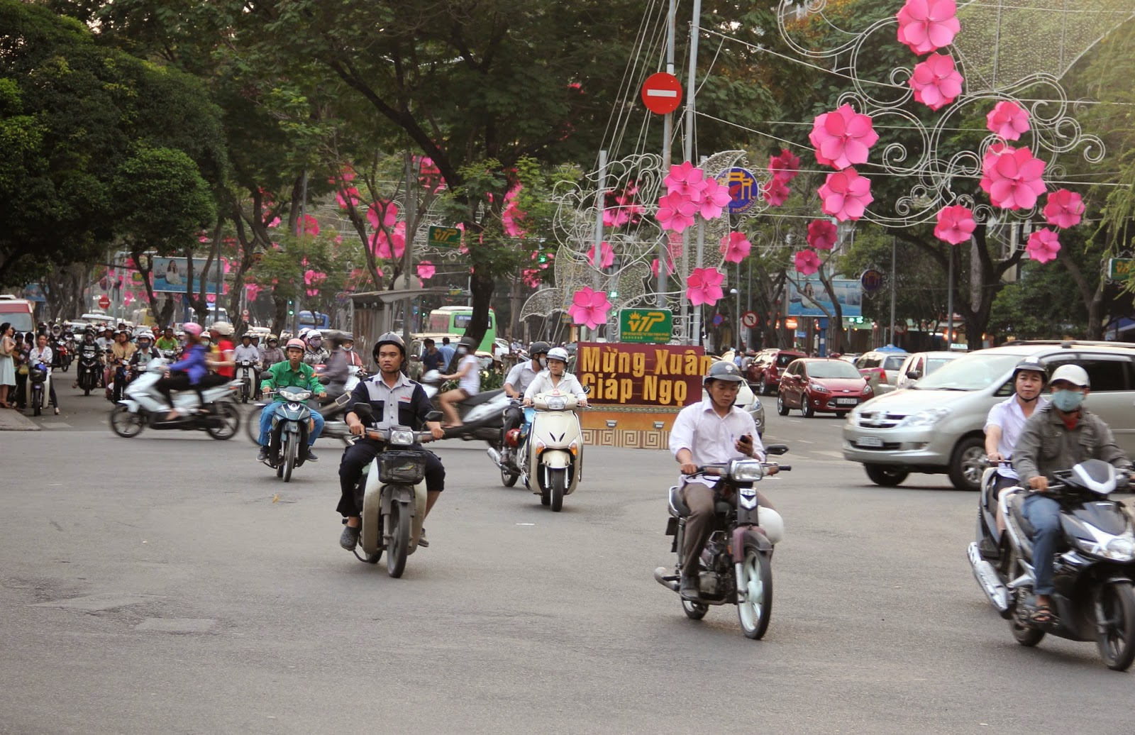Welcome to Ho Chi Minh City-motorbike traffic and Tet holiday decorations.