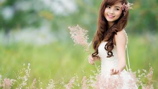 Na imagem: Uma garota asiática delicada em um gramado verde olhando para o lado com um sorriso no rosto e as mãos erguidas. Parece uma princesa.