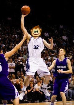 Action photo of a basketball player going up for a jump shot. He has the head of the Greasemonkey logo (a smiling monkey)