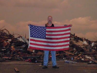 Man displays American flag amid tornado debris