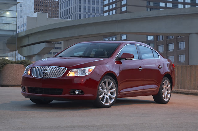 Red 2013 Buick LaCrosse on rooftop garage against downtown buildings