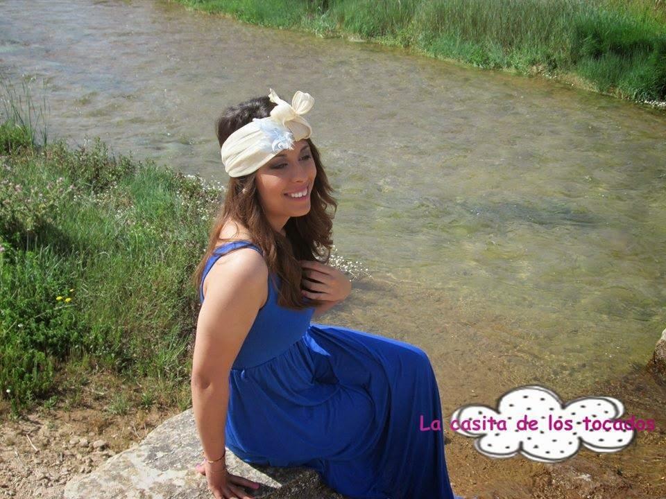 turbante en color beige con plumas a juego con vestido largo en azulón