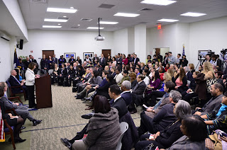 USCIS staff, community leaders, and members of the media listen to opening remarks