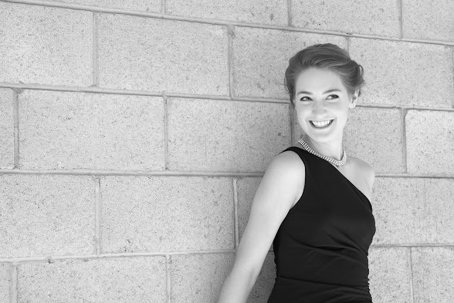 Singer in a black dress and pearls smiling and leaning against a cinder block wall.