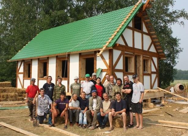 Команда строителей перед готовым домом