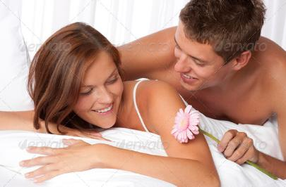 Happy_man_and_woman_lying_down_in_bed_together - 4 Tantric Sex Exercises for Couples or Singles