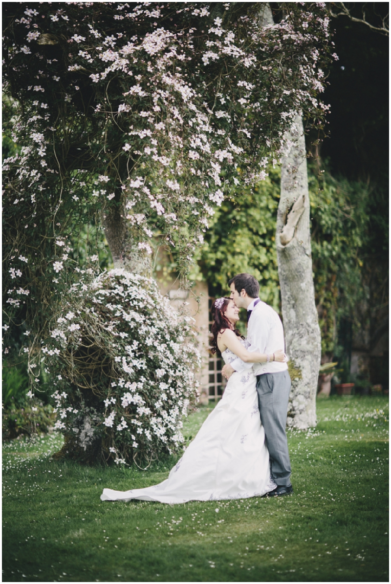 Couple standing under clematis after wedding