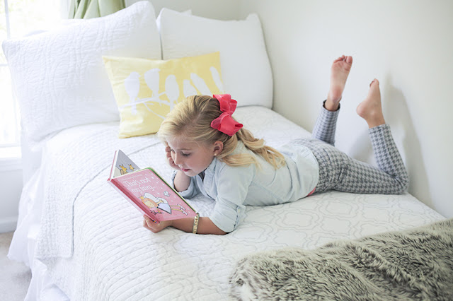 Amy West's daughter Sienna reading book on bed