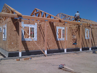 Pre-cut engineered roof trusses going on top of wall panels
