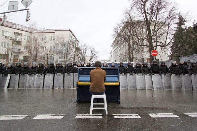 Мужчина играет на пианино для милиции. Киев, 2013 год.