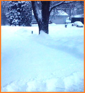 Long, mostly unshoveled driveway.  A slight area at the very bottom of the image shows a very thick cutting of snow.