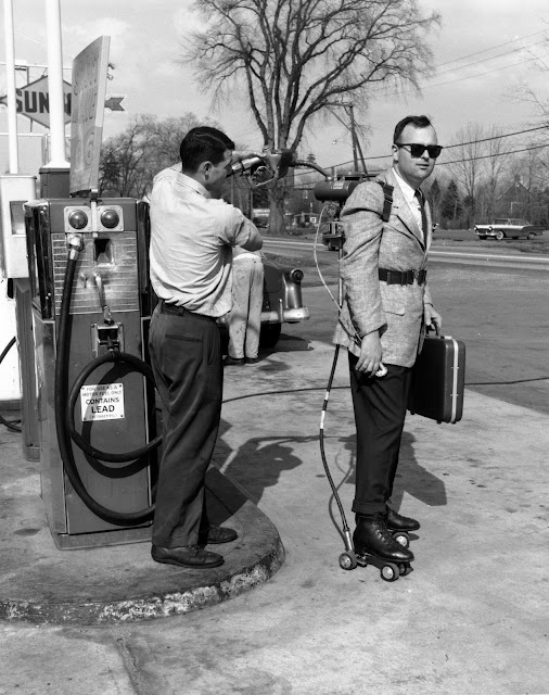 Gas-powered roller skates 11th May 1961: Salesman Mike Dreschler has his motorised roller skates refuelled at a petrol station near Hartford, Connecticut.