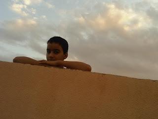 Un niño saharaui tras una pared de adobe