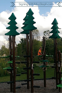 3 year old climbing fake trees at the playground