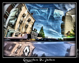A street scene reflected in the window of a car
