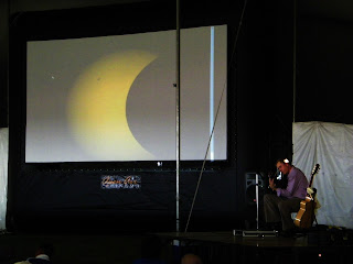 A guitarist entertains the crowd while the annular eclipse is projected
