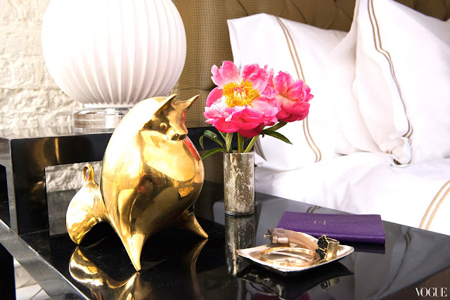 close up of Zani Gugelmann's night stand with a brass bull sculpture and flowers
