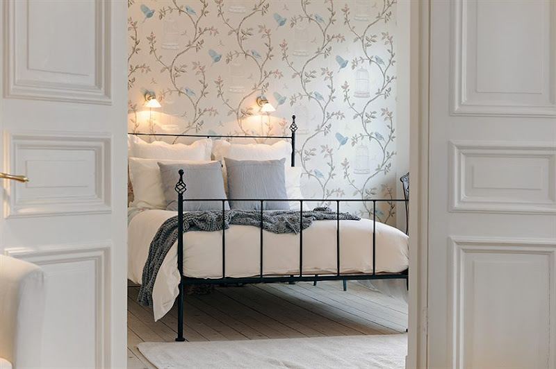 Bedroom in a Swedish apartment with iron bed frame, wall mounted lights, wall covered in a delicate wallpaper with a floral pattern with birdcages