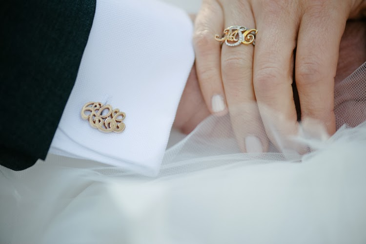 father and daughter hold hands with matching monogram jewelry