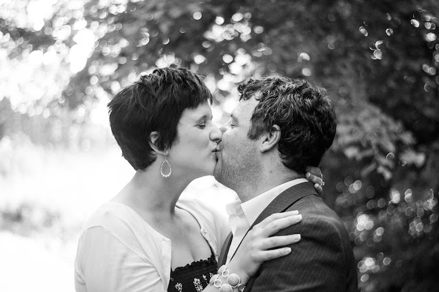 black and white of husband and wife kissing