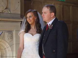 Bride standing at church with her father, wearing her white dress