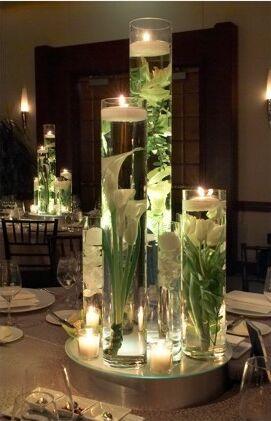 si quieres darle mas importancia al centro de mesa jarrones altos sobre una base de espejo en este caso rellenos con calas agua y velas