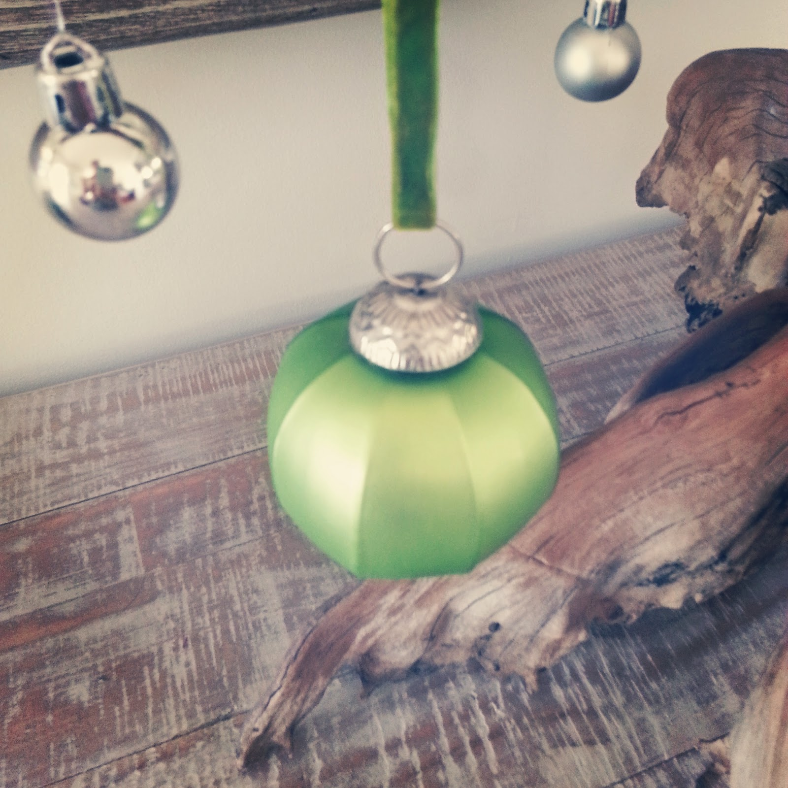 driftwood with green glass christmas ornaments coastal style home