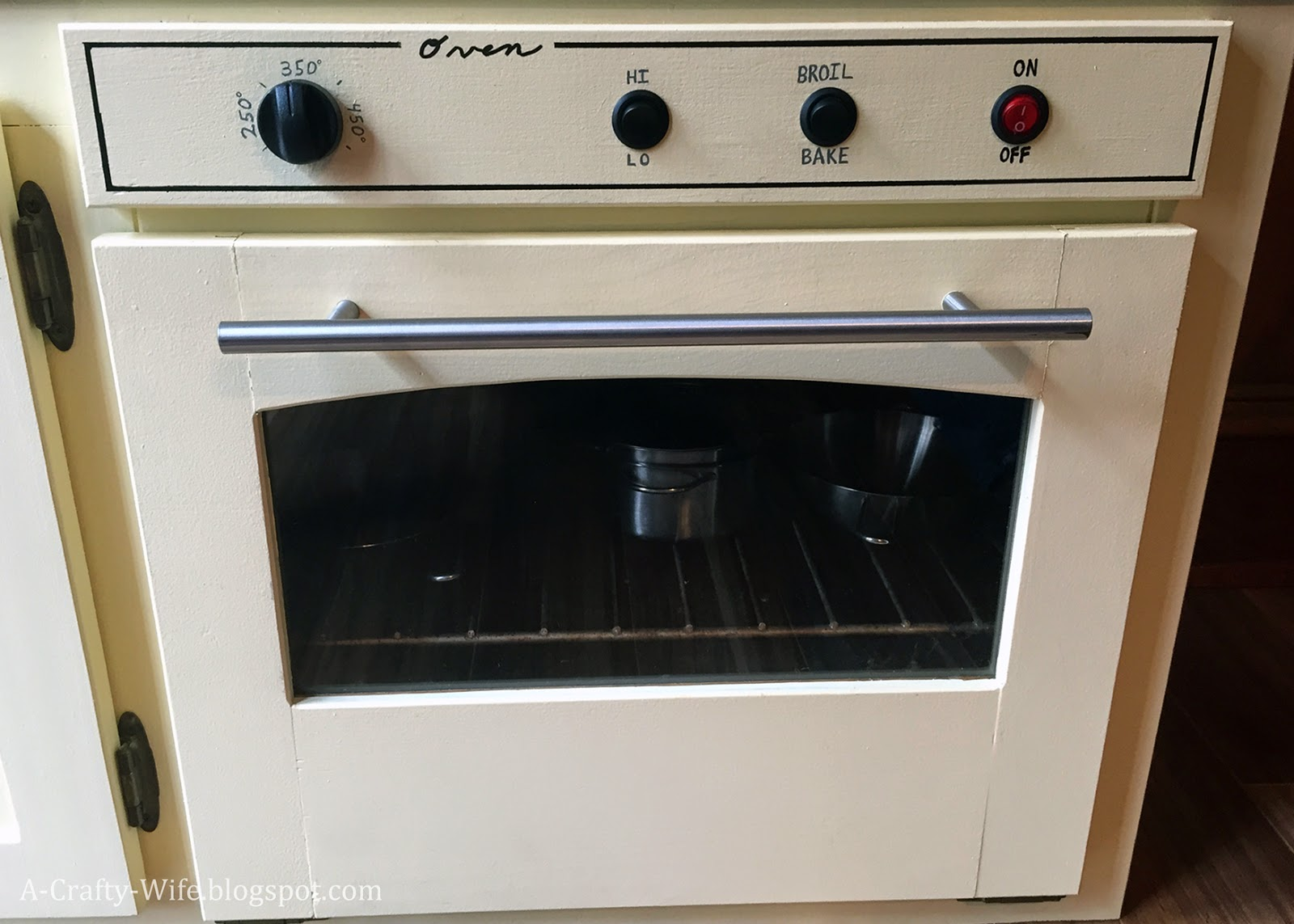 Use space heater buttons to make oven controls for toddler play kitchen from old cabinet.