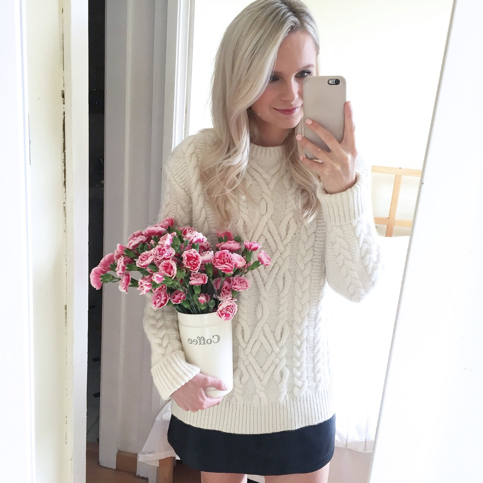 a young women swearing ivory cable knit sweater and holding pink flowers takes a photo of herself in a mirror