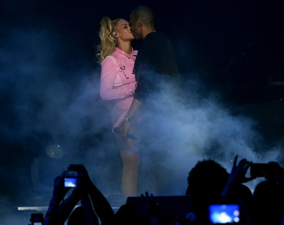 Jay Z kisses his wife while they perforned on stage