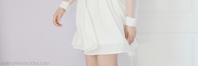 Close-up of the flowy white hem on the long sleeve mesh-paneled white dress from Fanewant on Storenvy.