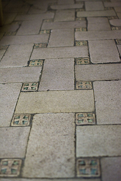 Cross pattern using rectangular stones on the church floor with smaller green tiles