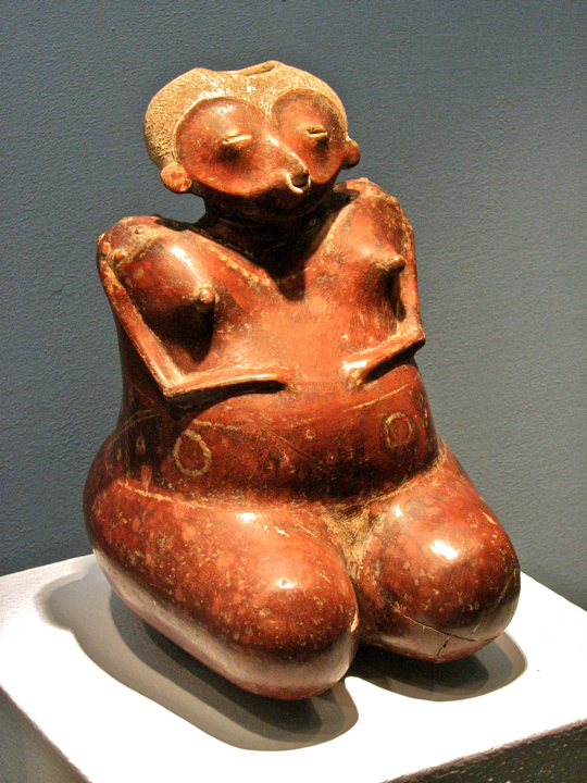 Pregnant figure is nude, except for tattoos, a necklace, and a nose ring.