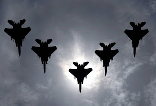 Five F-15 Jets flying in a V formation, blotting out the sun