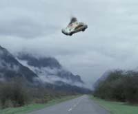 Detalle de una captura de la película, que muestra un coche en el aire, con fuego y humo saliendo de su interior