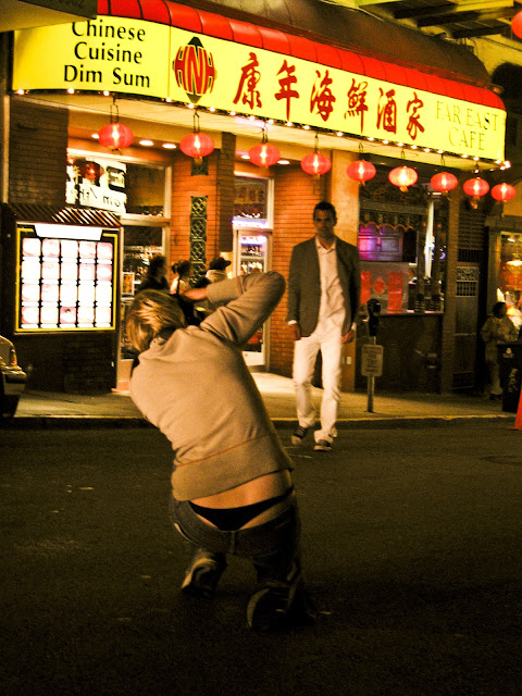 A kneeling photographer's black thong underwear are exposed during a photo shoot on the street in San Francisco's Chinatown.