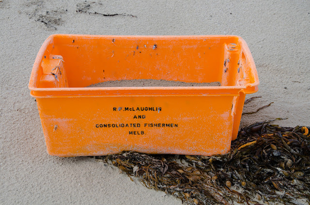 orange fishing tub washed up on beach