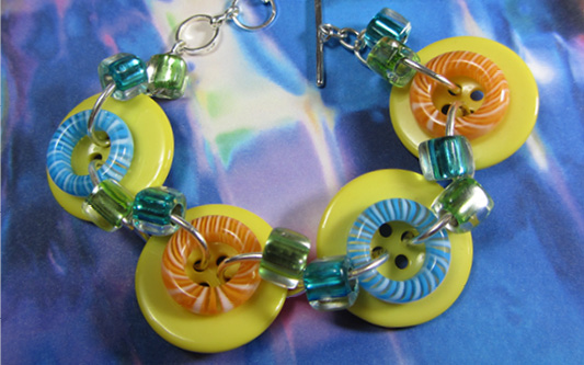 Bold bracelet has big yellow buttons accented with donut beads and smaller shiny beads