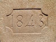 Detall de la dovella gravada amb l'any 1843 de sobre el portal de la capella de Sant Josep