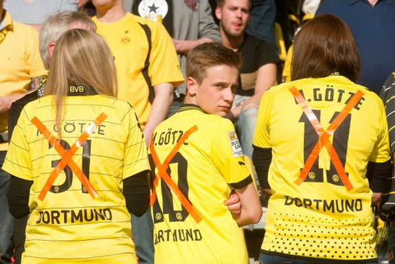 Dortmund fans wear Mario Götze shirts with his name crossed out