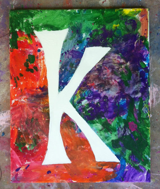 """finished product of paint project- letter """"K"""" in white with abstract paint colors covering canvas"""