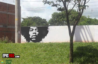 partial jimi hendrix graffiti mural with tree in background