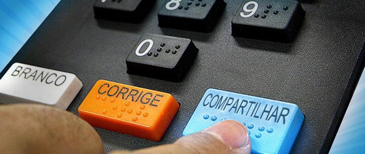 """Uma urna eletrônica de votação mostrando uma mão apertando o botão """"Confirmar"""", porém no lugar dessa palavra, está escrito """"Compartilhar""""."""