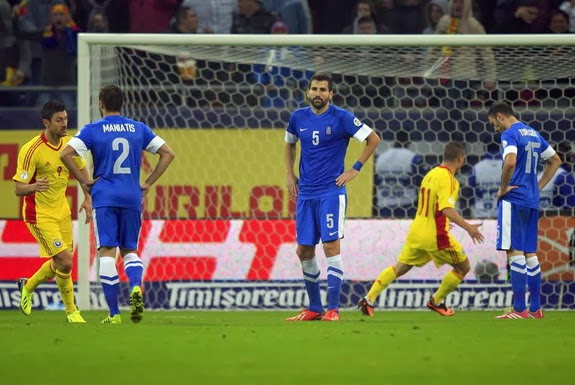 Greece player Vasilios Torosidis reacts after scoring an own goal against Romania