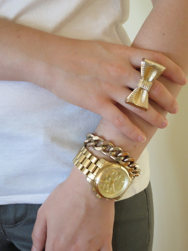 A gold Michael Kors watch, chain bracelet and bow ring.