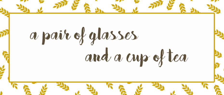 a pair of glasses and a cup of tea